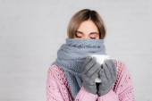 Young woman wrapped in warm scarf holding cup on white background
