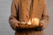 Oříznutý pohled na hořící svíčky na dřevěné desce v rukou ženy v šátku a svetru rozmazané na bílém pozadí