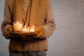 Oříznutý pohled na hořící svíčky v rukou ženy v teplém oblečení a rukavice na šedém pozadí
