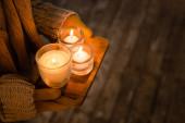 Oříznutý pohled na ženu v pletených a rukavicích držících hořící svíčky na dřevěné desce