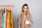 Usmívající se žena v pletené a rukavice stojící u ramínka stojan se svetry na bílém pozadí