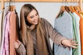 Mladá žena při pohledu na pletené svetry na věšák stojan na bílém pozadí