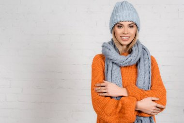 Stylish woman in cozy sweater, hat and scarf smiling at camera on white background stock vector
