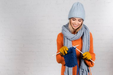Young positive woman in warm gloves an sweater knitting with wool thread on white background stock vector