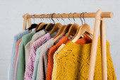 Hangers with colorful sweaters on hanger rack on white background