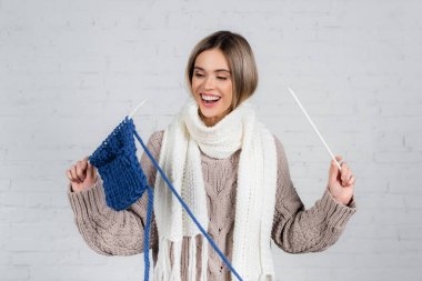 Positive woman in scarf and sweater holding yarn and knitting needles near on white brick wall stock vector