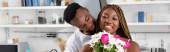 Usmívající se afro-americká žena držící kytici poblíž přítele v kuchyni, prapor