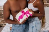 Ausgeschnittene Ansicht der Gegenwart in den Händen von sexy afrikanisch-amerikanischen Paar auf dem Bett auf verschwommenem Hintergrund
