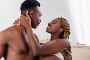 Smiling african american woman in bra embracing neck of shirtless boyfriend at home stock vector