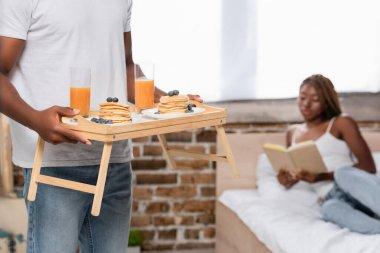 Afro-Amerikalı bir adam kahvaltı tepsisi tutuyor. Yanında da kitabı bulanık arka plan olan bir kız arkadaş.