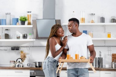Smiling african american woman hugging boyfriend with delicious breakfast and orange juice on tray in kitchen stock vector