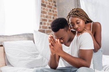 African american woman hugging sad boyfriend on bed stock vector
