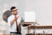 Seriöser Architekt mit Brille zeigt mit Bleistift auf Hausmodell