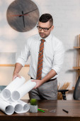 architect in eyeglasses holding blueprint while standing at workplace