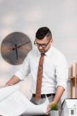 seriózní architekt v brýlích s plánem v úřadu