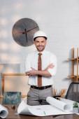 glücklicher Architekt mit Helm, der mit verschränkten Armen neben Bauplänen auf dem Schreibtisch steht