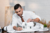 concentrated architect drawing on blueprint near house model