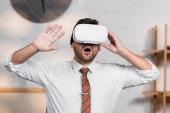 užaslý architekt gestikuluje při použití vr headsetu v kanceláři