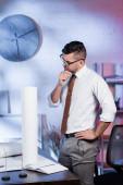 přemýšlivý architekt stojící s rukou na boku na pracovišti v kanceláři