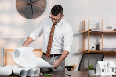 Architect holding blueprint near house model and vr headset on desk stock vector