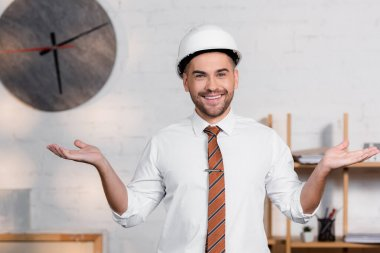 Cheerful architect in helmet standing with open arms and smiling at camera stock vector