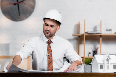 Concentrated architect in helmet working on project near house model stock vector