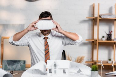 Architect touching vr headset at workplace near blueprint and house model stock vector