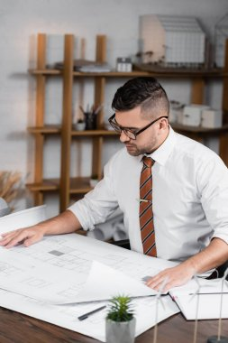 Concentrated architect working on project in office stock vector