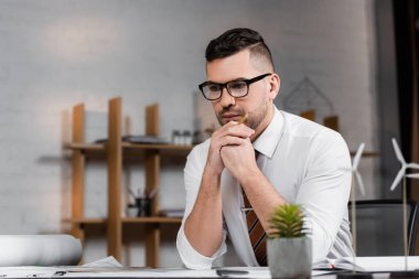 Thoughtful architect sitting at workplace near models of wind turbines on blurred foreground stock vector