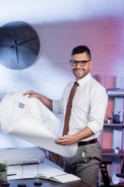 Happy architect looking at camera while holding blueprint near models of wind turbines on desk stock vector
