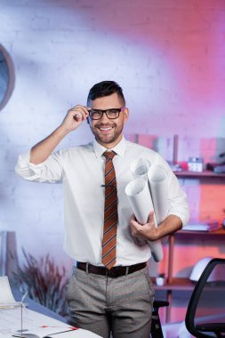 Architect adjusting eyeglasses while standing with rolled blueprints and smiling at camera stock vector