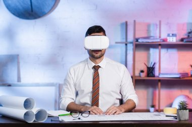 Architect in vr headset sitting at workplace near blueprints stock vector