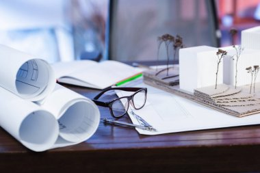 Selective focus of eyeglasses near house models and blueprints on desk in office, blurred background stock vector