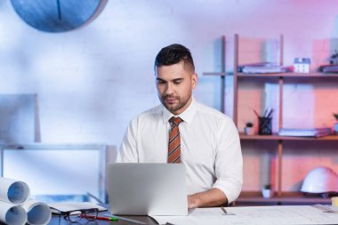 Concentrated architect working on laptop near blueprints on desk stock vector
