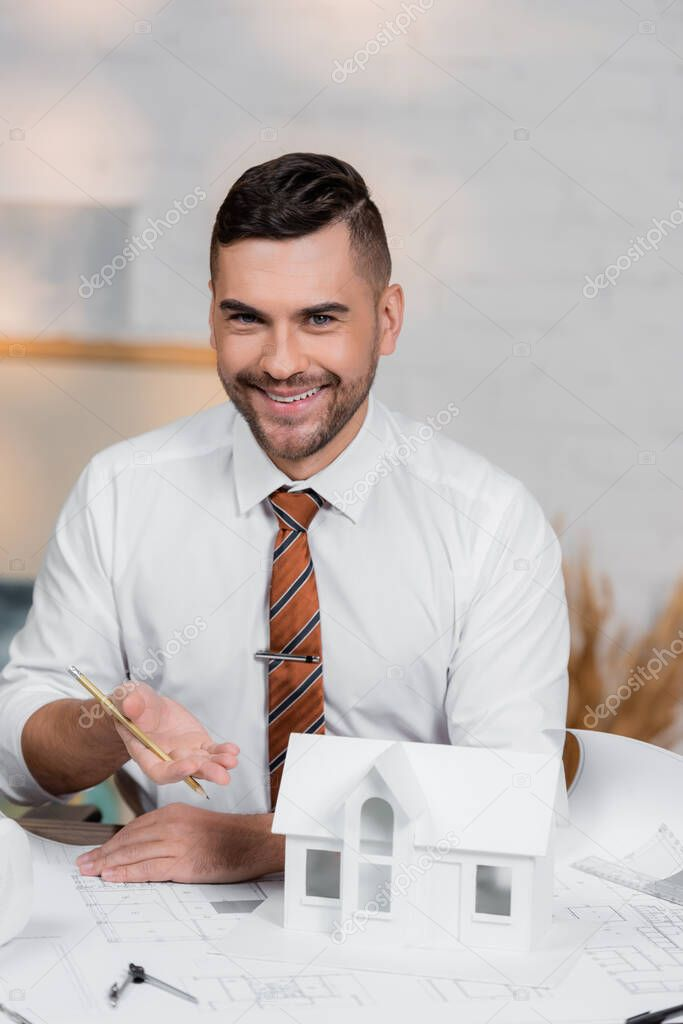 Smiling architect looking at camera while pointing at house model stock vector