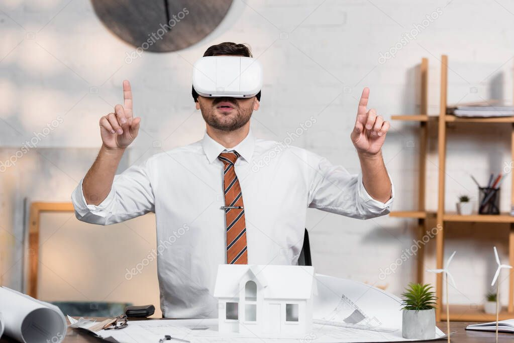 Architect in vr headset pointing with fingers while sitting at workplace near house model stock vector