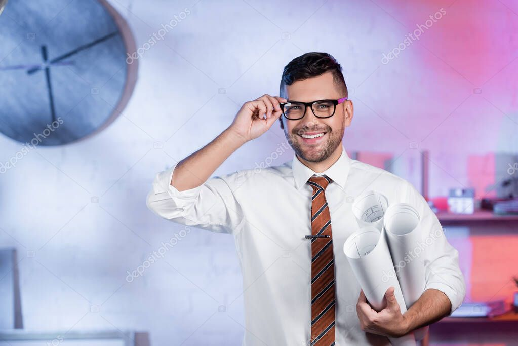 Cheerful architect holding rolled blueprints and adjusting eyeglasses while looking at camera stock vector