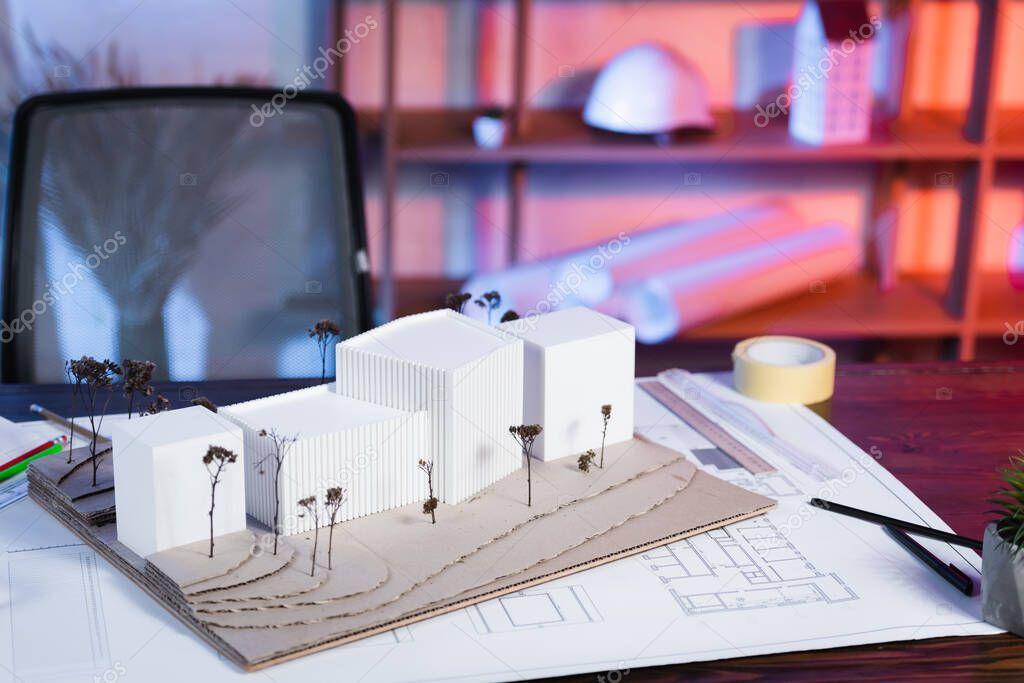 Constructions models near blueprint on desk in architectural bureau stock vector