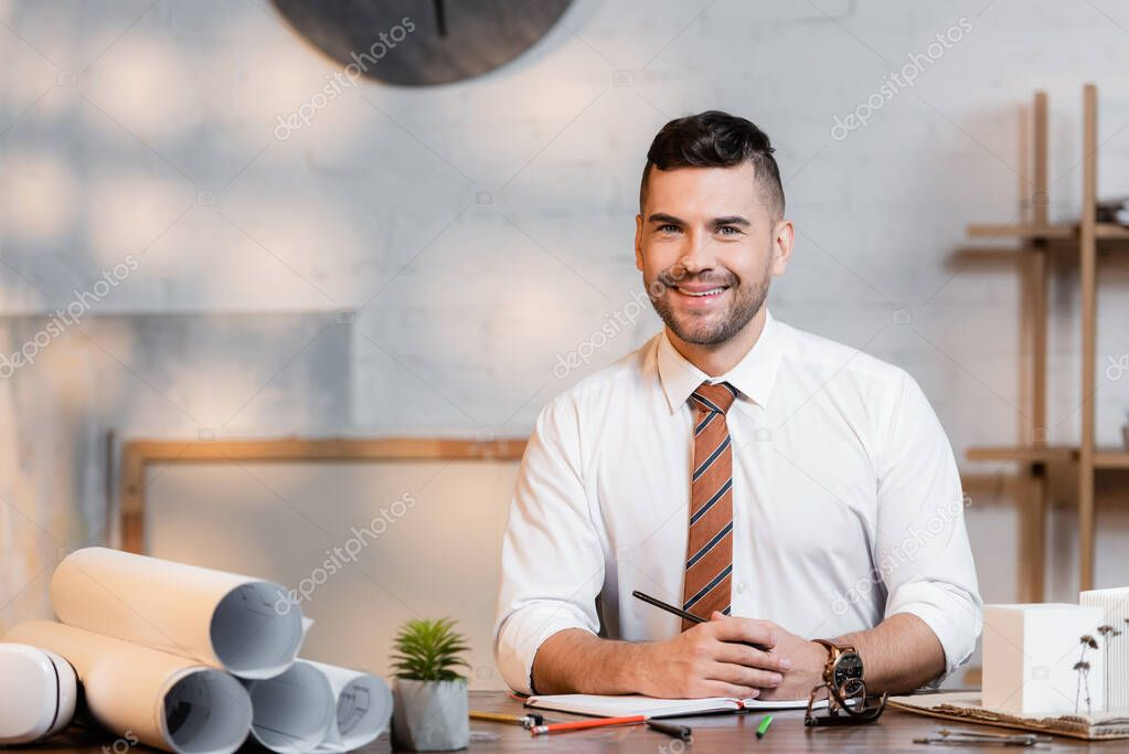 Smiling architect looking at camera while sitting at workplace near rolled blueprints stock vector