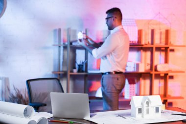 Selective focus of laptop, house model and blueprints on desk, and architect near rack on blurred background stock vector
