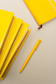 pohled shora na žluté diáře a pero izolované na šedé