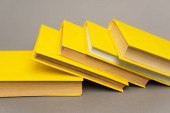 stacked yellow notebooks and books on grey