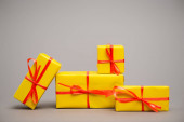 wrapped yellow presents with red ribbons on grey