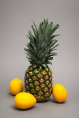 whole ripe and fresh pineapple near yellow lemons on grey
