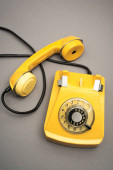 felső nézet retro és sárga telefon szürke háttér