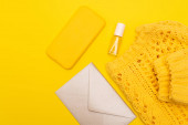 horní pohled na láhev s lakem na nehty, smartphone v případě, že v blízkosti oblečení a obálka izolované na žluté