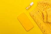 vrchní pohled na láhev s lakem na nehty, smartphone v případě, že v blízkosti jumper izolované na žluté
