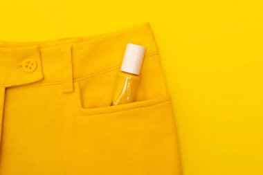 Top view of glass bottle with nail polish in pocket of pants isolated on yellow stock vector