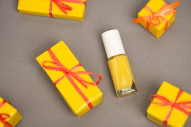 High angle view of wrapped yellow gift boxes near bottle with nail polish on grey stock vector