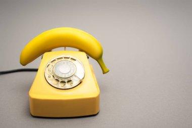 Yellow banana on retro telephone on grey background stock vector
